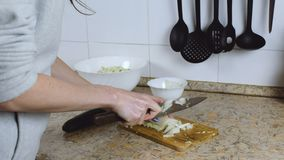 La donna irriconoscibile ha tagliato il cavolo cinese sul tagliere in tavolo da cucina Le mani si chiudono in su archivi video