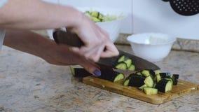 La donna irriconoscibile ha tagliato il cetriolo sul tagliere sul tavolo da cucina passa il primo piano Front View video d archivio