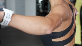La donna irriconoscibile sportiva in abiti sportivi spande le sue mani al lato con le teste di legno in palestra archivi video