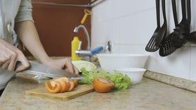 La donna irriconoscibile taglia i pomodori su un tagliere nella cucina Le mani si chiudono in su archivi video