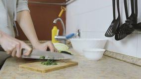 La donna irriconoscibile taglia l'aneto su un tagliere nella cucina Le mani si chiudono in su video d archivio