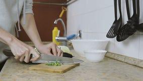 La donna irriconoscibile taglia una cipolla verde su un tagliere nella cucina Le mani si chiudono in su stock footage