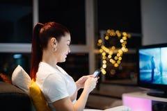 La donna ispana invia le chiacchierate del messaggio di testo sul telefono cellulare fotografie stock