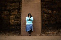 La donna ispana prega dalla parete fotografia stock libera da diritti
