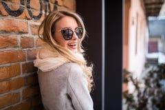 La donna ispirata all'aperto sul sole brillante della molla, gode della sua vita vicino al muro di mattoni immagine stock libera da diritti