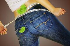 La donna in jeans che si misurano nastro e perde il peso Fotografie Stock