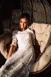 La donna, la sposa si siede su un'oscillazione di vimini Giorno di estate pieno di sole fotografie stock