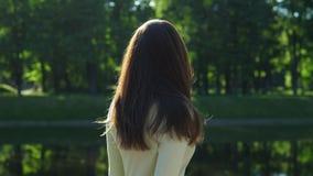 La donna lancia i suoi capelli brillanti lunghi contro fogliame verde archivi video