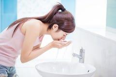 La donna lava il suo fronte fotografia stock