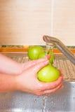 La donna lava una mela verde fotografia stock