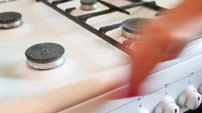 La donna lava una stufa di gas nella pulizia della cucina stock footage