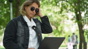 La donna lavora ad un computer portatile mentre si siede nel parco stock footage