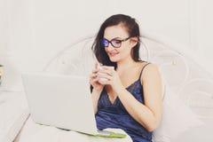 La donna legge dal pc della compressa a letto, alta chiave Fotografie Stock Libere da Diritti