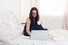 La donna legge dal pc della compressa a letto, alta chiave Fotografia Stock