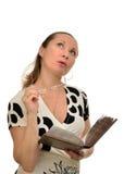 La donna leggendo un libro e perso nel pensiero ha decollato i suoi vetri Immagini Stock