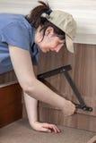 La donna lei stessa monta la mobilia, lei avvita la cerniera di sollevamento del letto Immagine Stock