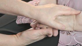 La donna lenisce la donna anziana durante lo sforzo stock footage