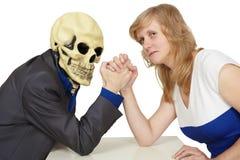 La donna lotta contro la morte su bianco Immagini Stock