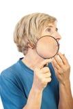 La donna maggiore analizza le sue grinze con la lente di ingrandimento Fotografia Stock Libera da Diritti