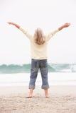 La donna maggiore con le braccia Outstretched sulla spiaggia Immagini Stock Libere da Diritti