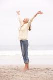 La donna maggiore con le braccia Outstretched sulla spiaggia Fotografia Stock