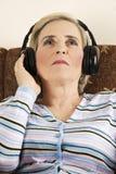 La donna maggiore di bellezza ascolta musica Immagini Stock Libere da Diritti