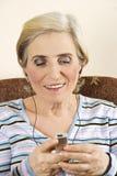 La donna maggiore felice ascolta musica Immagini Stock