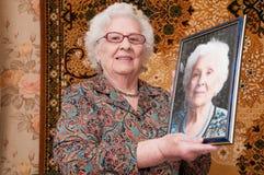La donna maggiore mostra il suo ritratto Immagine Stock Libera da Diritti