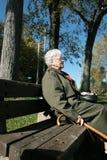 La donna maggiore si distende su un banco Fotografia Stock Libera da Diritti