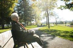 La donna maggiore si siede su un banco Immagini Stock Libere da Diritti