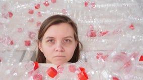 La donna malata disidratata sta trovandosi in un mucchio delle bottiglie di plastica Problema dell'inquinamento ambientale Immond archivi video