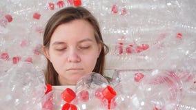 La donna malata disidratata sta trovandosi in un mucchio delle bottiglie di plastica Problema dell'inquinamento ambientale Immond video d archivio