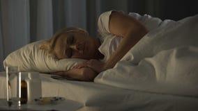 La donna malata sola che esamina il telefono cellulare che conta i minuti fino a dolore allevia archivi video