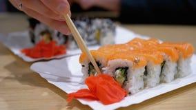 La donna mangia i sushi Rolls con i bastoncini in un ristorante giapponese archivi video