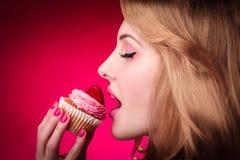 La donna mangia il bigné con la fragola Fotografia Stock Libera da Diritti