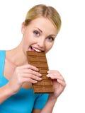 La donna mangia la barra di cioccolato Fotografia Stock
