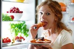 La donna mangia la stola di notte il frigorifero Immagini Stock Libere da Diritti