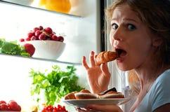 La donna mangia la stola di notte il frigorifero Fotografie Stock Libere da Diritti
