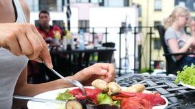 La donna mangia le verdure arrostite con una fine della forcella su contro il contesto degli ospiti archivi video