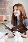 La donna mantiene il menu per fare un ordine Fotografia Stock