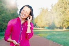La donna matura ascolta musica prima o dopo il trotto nel parco immagini stock