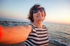 La donna matura attraente alla moda 50-60 fa il selfie sul pho mobile Fotografia Stock Libera da Diritti