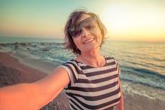 La donna matura attraente alla moda 50-60 fa il selfie sul pho mobile Immagini Stock Libere da Diritti