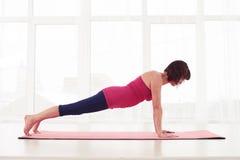 La donna matura dentro spinge verso l'alto la posizione su una stuoia di yoga nella palestra Fotografia Stock