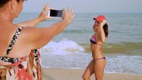 La donna matura fa una foto sul suo ` abbronzato la s Smartphone della figlia nel costume da bagno sulla riva di mare video d archivio