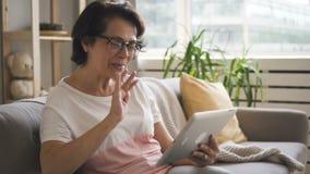 La donna matura felice sta facendo video la chiamata video d archivio