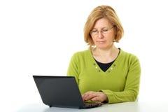 La donna matura lavora al suo computer portatile,   Immagini Stock Libere da Diritti