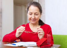 La donna matura legge la fattura Fotografia Stock Libera da Diritti