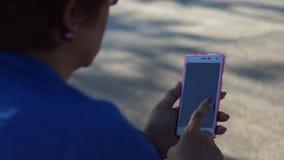 La donna matura passa in rassegna Internet con l'uso dello smartphone mobile stock footage