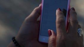 La donna matura passa in rassegna Internet con l'uso dello smartphone mobile video d archivio